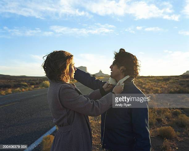 couple by desert road, woman adjusting man's  collar, man pointing - adjusting stock pictures, royalty-free photos & images
