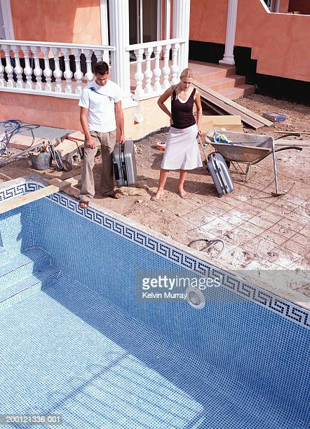 couple by empty pool outside apartment building under construction - inconvenience stock pictures, royalty-free photos & images