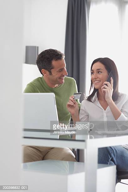 Couple by laptop, woman holding credit card and telephone, smiling