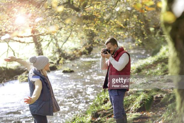 Couple by river taking photo