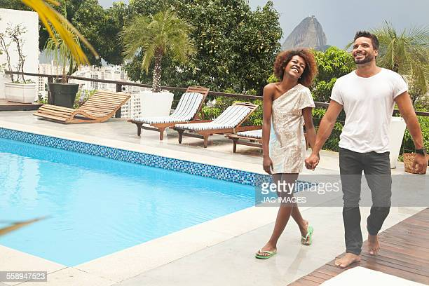 couple by terrace pool, sugarloaf mountain in background, rio, brazil - honeymoon stock pictures, royalty-free photos & images