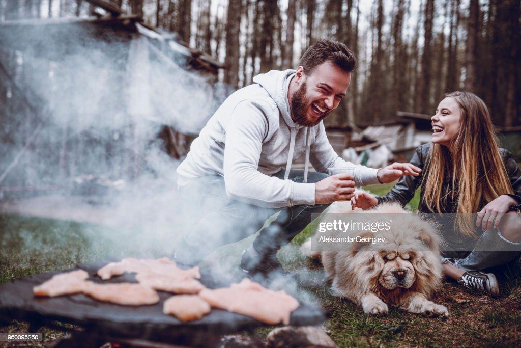 Paar Camper Barbecue machen und Spaß mit Hund : Stock-Foto