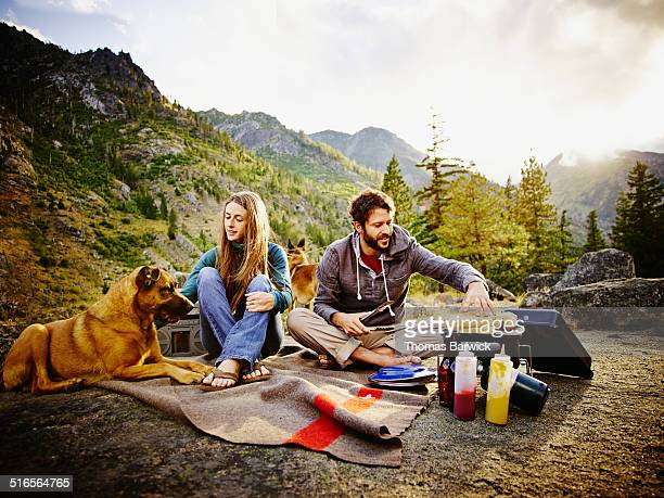 couple camping and barbecuing dinner at sunset - one animal stock pictures, royalty-free photos & images