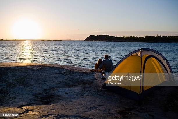 Couple camping by sea at sunset