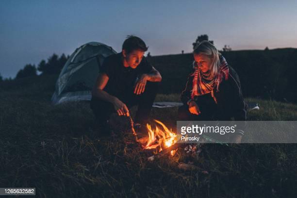 星空の下で夜に山でキャンプするカップル - 焚き火 ストックフォトと画像