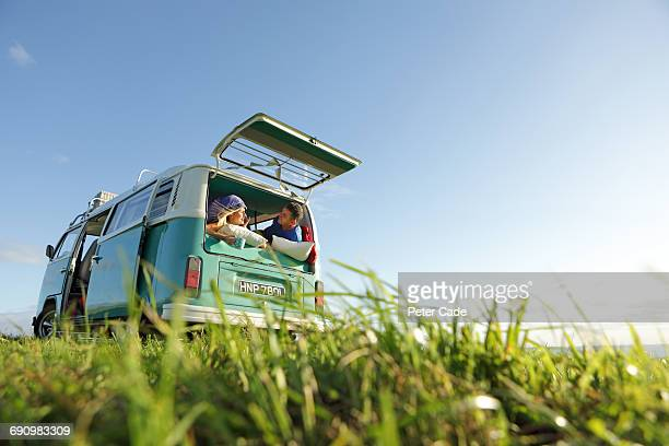 couple camping in van in field by sea - camper van stock pictures, royalty-free photos & images