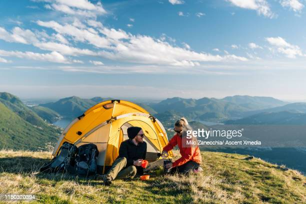 couple camping on mountain top, prepare food and beverages next to tent - tent stock pictures, royalty-free photos & images