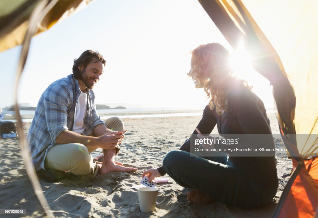 Camping Playing Cards On Beach At Sunset Stock Photo