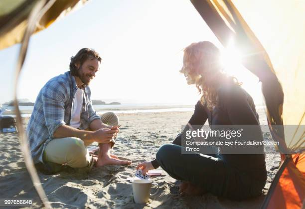 couple camping playing cards on beach at sunset - outdoor pursuit stock pictures, royalty-free photos & images