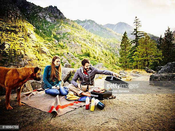 Couple camping with dog barbecuing at sunset