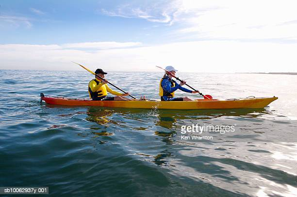 Couple canoeing at sea, side view