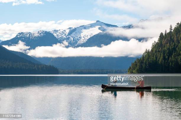 couple canoeing on lake against beautiful mountain - whistler british columbia stock pictures, royalty-free photos & images