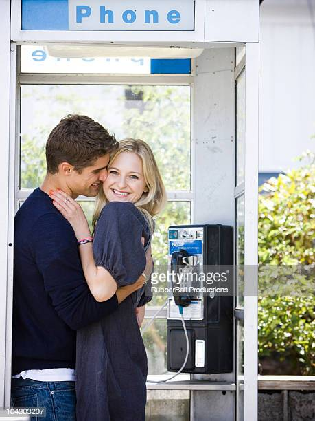 couple canoodling in a phone booth
