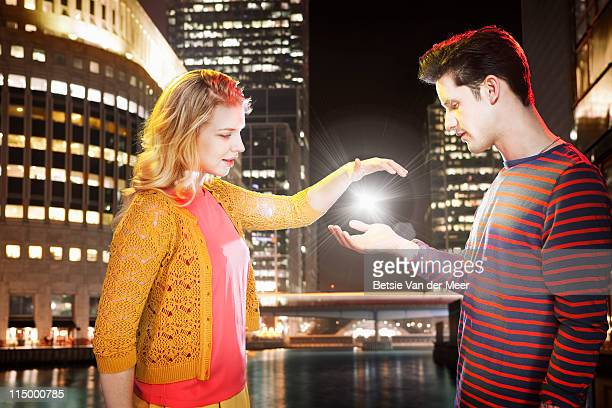 couple capturing light between their hands. - newpremiumuk stock pictures, royalty-free photos & images