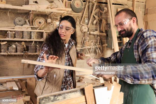 Couple carpenter workers making a frame in their workshop