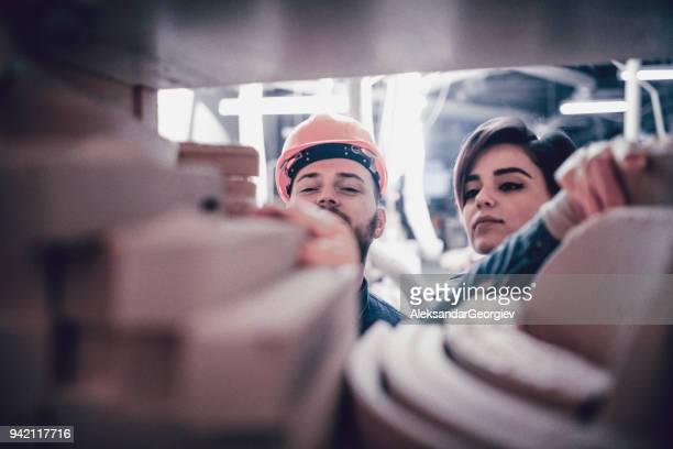 Couple Carpenters Arrange the Wooden Parts on Shelf in Workshop
