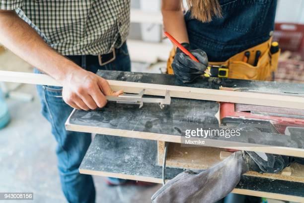 paar tischler mess holzbrett in der werkstatt - unterschicht stereotypen stock-fotos und bilder