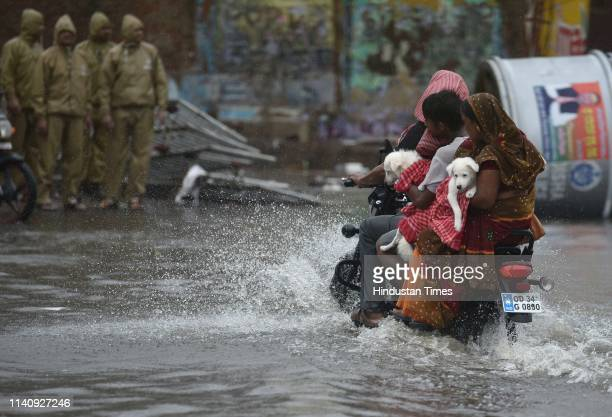 A couple carries their pets after the onset of cyclone Fani on May 3 2019 in Puri India Cyclone Fani on Friday lashed Odisha triggering heavy...