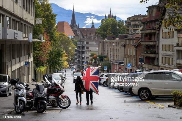 A couple carring a giant cushion bearing the Britain's Union Jack bought in a second hand shop is walking in a street of Lausanne on October 19 2019