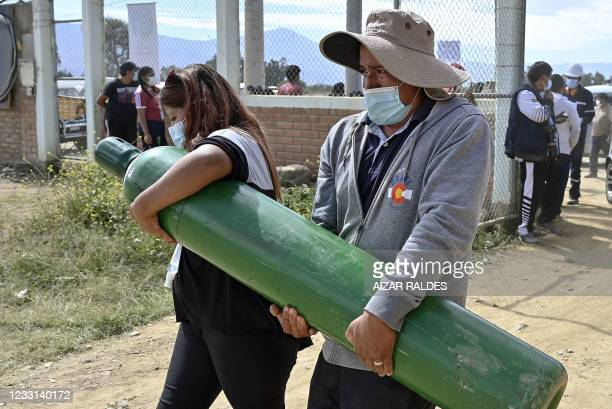Couple carry an empty oxygen tank to refill as they arrive to Valle Alto Medical Oxygen plant in Arbieto municipality, 50 km from Cochabamba, on May...