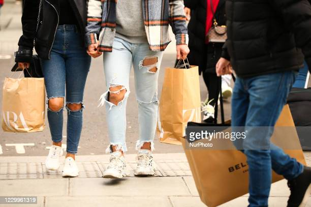 Couple carry bags from clothing retailer Zara along Oxford Street in London, England, on December 5, 2020. London has returned to so-called Tier 2 or...