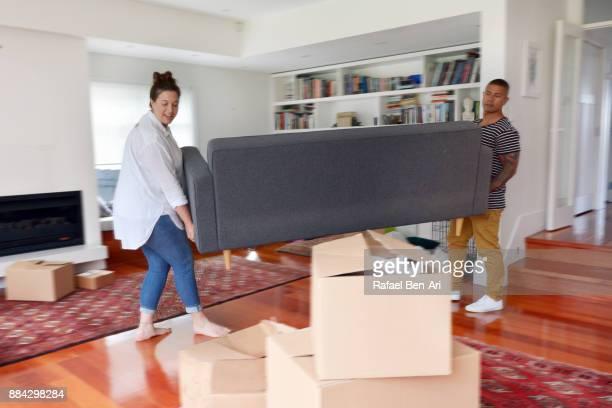 couple carrying a sofa into their living room during moving into a new home - rafael ben ari imagens e fotografias de stock