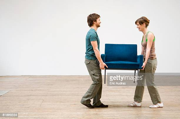 Couple carrying an armchair