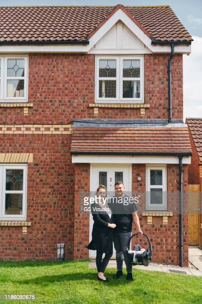 couple carrying baby in cradle in front of house - baby stock pictures, royalty-free photos & images