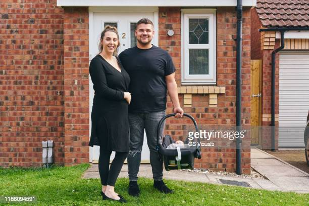 couple carrying baby in cradle in front of house - looking at camera stock pictures, royalty-free photos & images