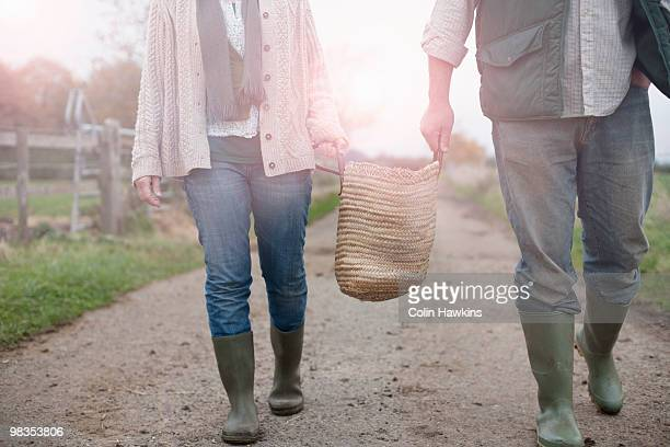 couple carrying basket in countryside