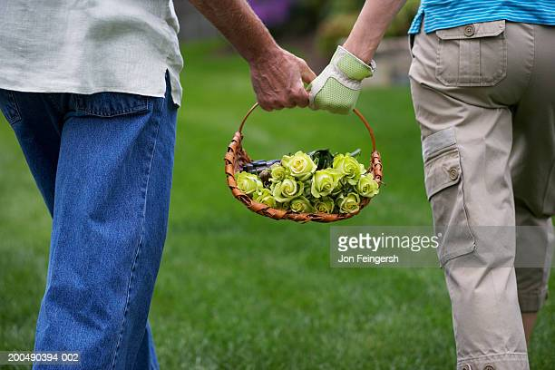 Couple carrying basket of flowers, close-up, rear view