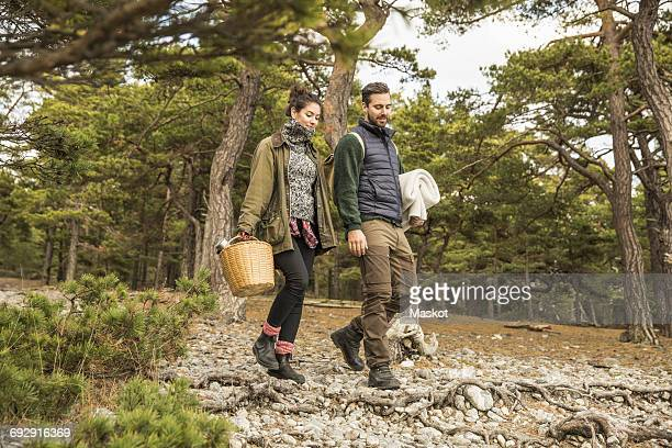 Couple carrying blanket and basket in forest