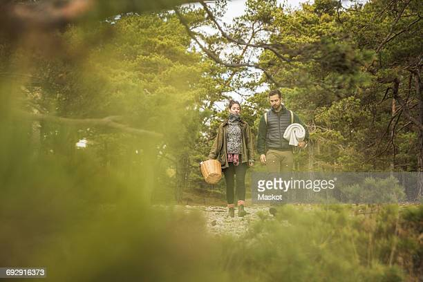 Couple carrying blanket and basket in forest seen through plants