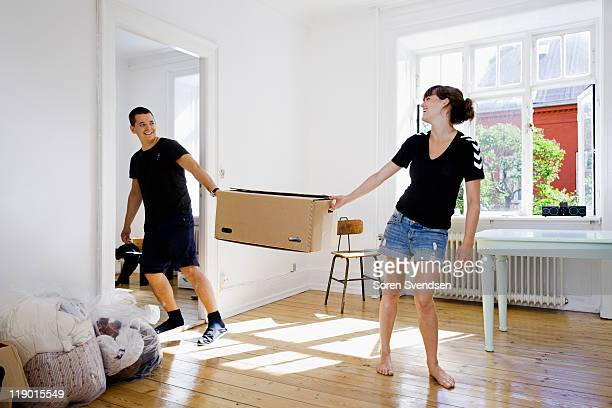 Couple carrying box in new home