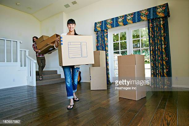 Couple carrying boxes in new home