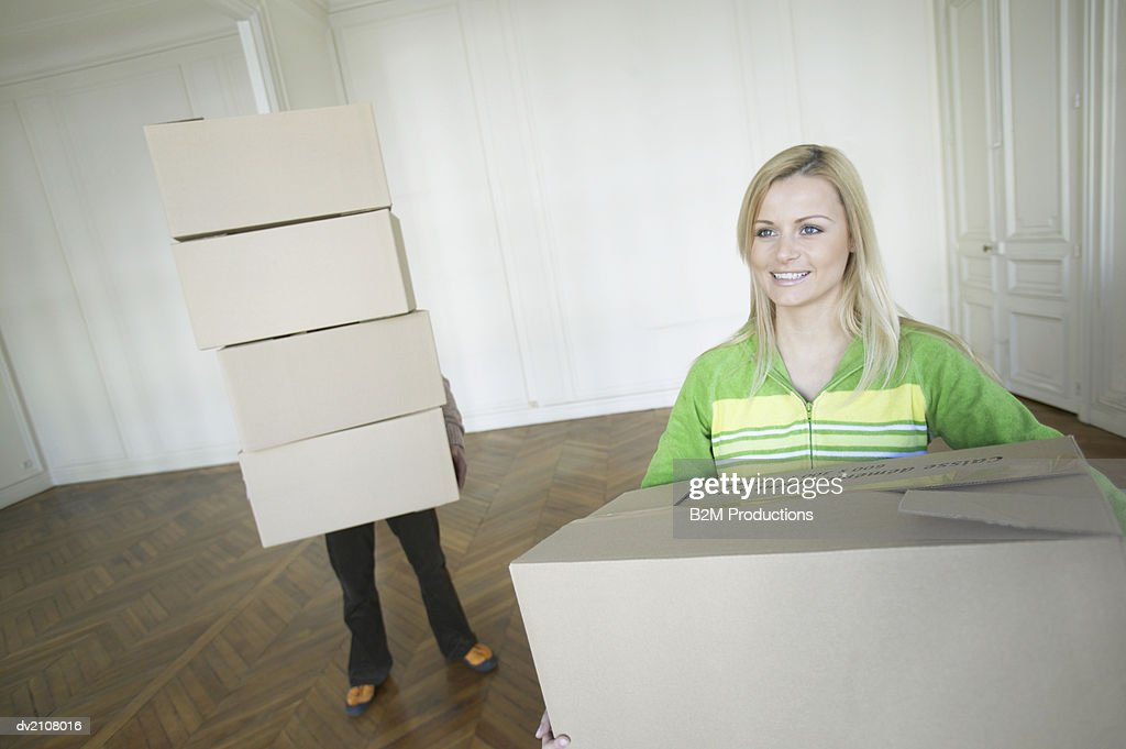 Couple Carrying Boxes Moving into a House : Stock Photo