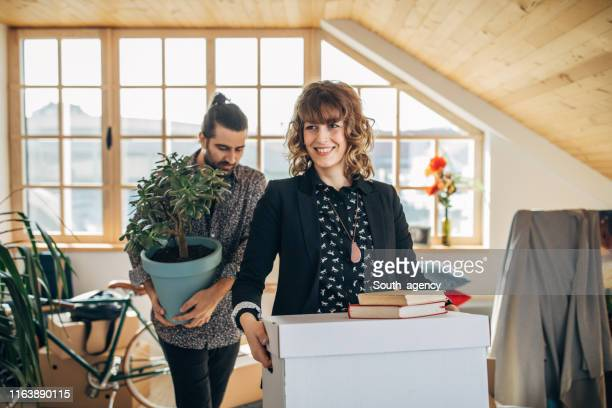 couple carrying cardboard boxes in new home - arranging stock pictures, royalty-free photos & images