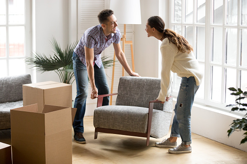 Couple carrying chair together, placing furniture moving in new home 938682838