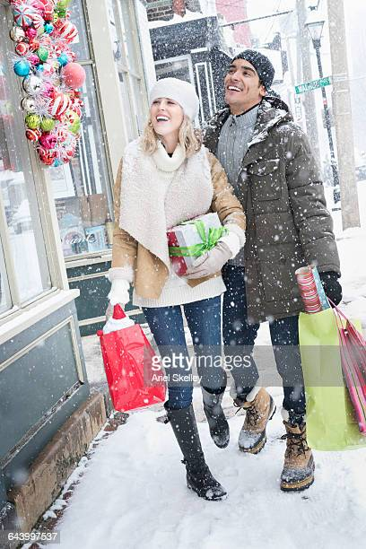 Couple carrying Christmas gifts in snow