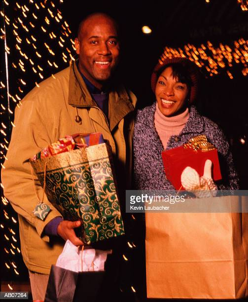 Couple carrying Christmas gifts, night