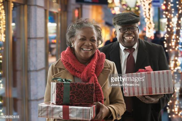Couple carrying Christmas gifts on city street