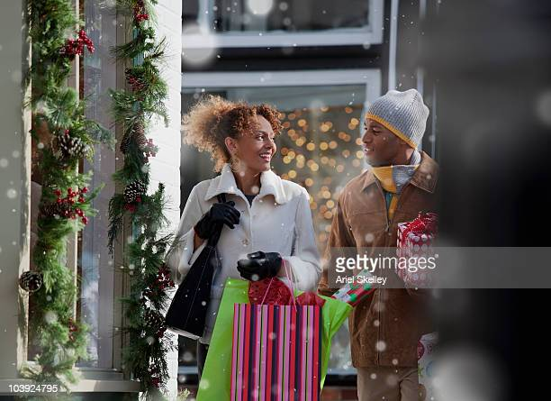 couple carrying christmas gifts outdoors - holiday shopping stock photos and pictures
