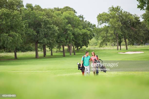 Couple carrying clubs walking on golf course together