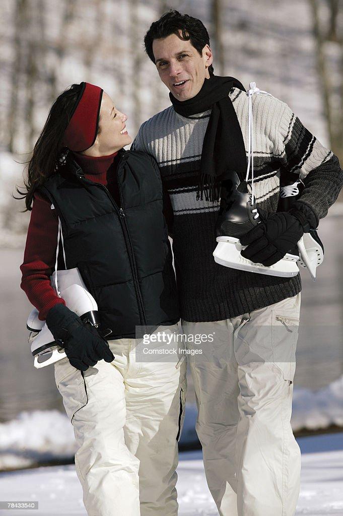 Couple carrying ice skates : Stockfoto
