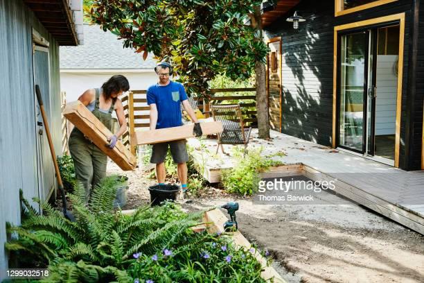 couple carrying lumber to build raised garden beds in backyard - nur erwachsene stock-fotos und bilder