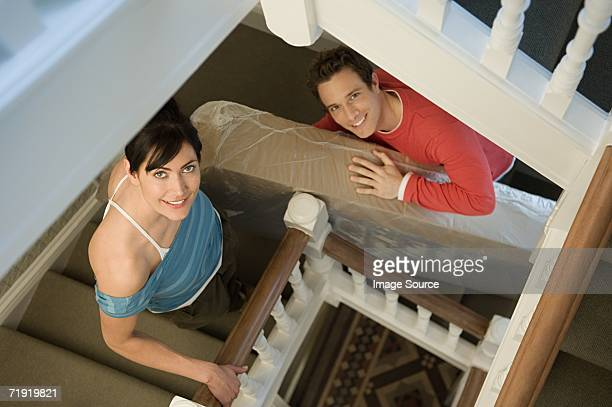 Couple carrying mattress up stairs