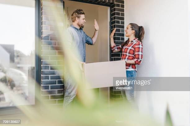 Couple carrying moving boxes into their new home, giving high five