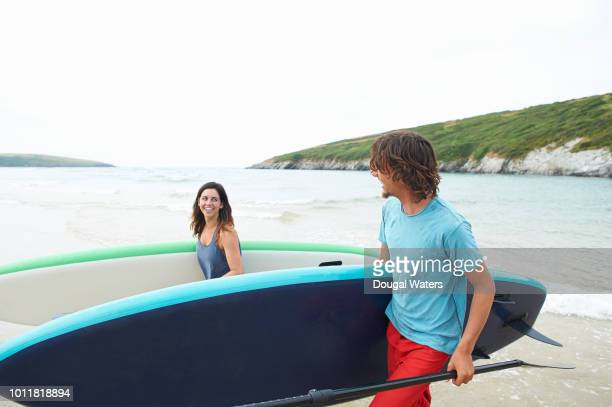 couple carrying paddle boards and chatting on beach. - dougal waters stock pictures, royalty-free photos & images