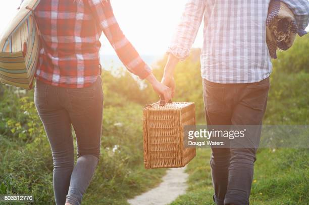 Couple carrying picnic hamper on coastal path.