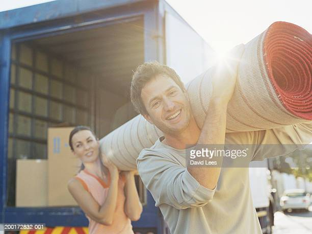 Couple carrying rug from removal van (focus on man smiling)